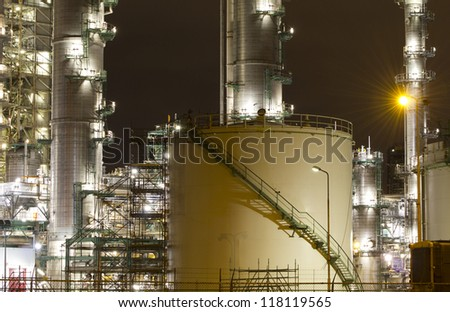 Petrochemical-tanks and a large oil-refinery plant at night - stock photo