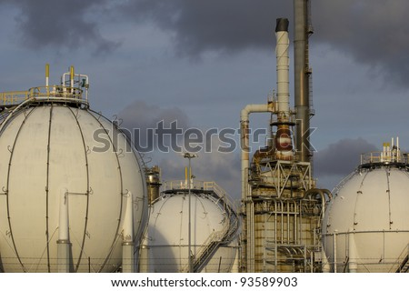 Petrochemical-tanks and a large oil-refinery-plant in the background. - stock photo