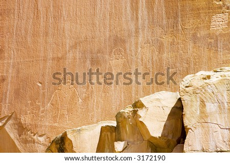 Petroglyph or rock carvings of Native Americans on a canyon wall in Utah, USA, representing animals, figures, sheep, snakes, wilderness - stock photo