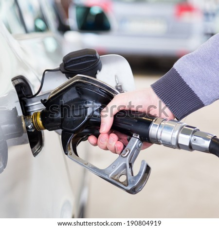 Petrol or gasoline being pumped into a motor vehicle car. Closeup of man pumping gasoline fuel in car at gas station.
