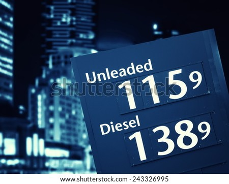 petrol prices on the fuel station on city background - stock photo