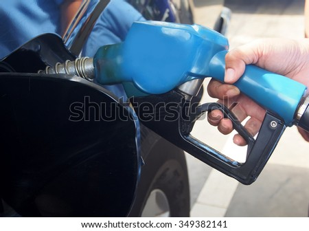 petrol pump filling at gas station hand holding fuel nozzle