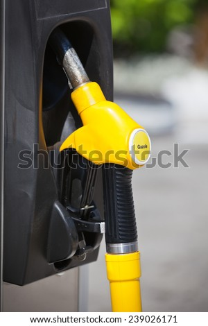 Petrol pump nozzle in a service station. Vertical shot