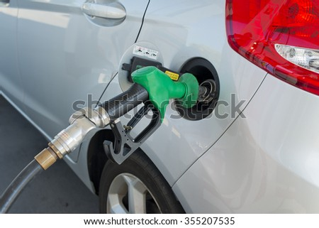 Petrol pump nozzle in car's petrol tank filling it up with petrol at a petrol station. Petrol pump hose is black rubber and nozzle is green. Part of car's tail light can be seen.  - stock photo