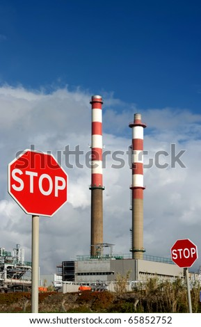 Petrol refinery with STOP signs in foreground - Energy waste concept. - stock photo