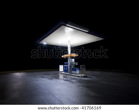 Petrol station at night with traffic in movement - stock photo