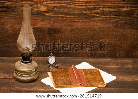 petroleum lamp, old book and pocket watch over a vintage background - stock photo