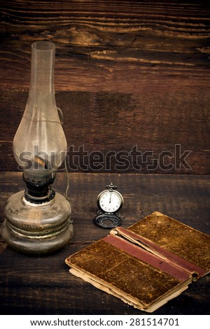 petroleum lamp,old pocket watch and old book  - stock photo