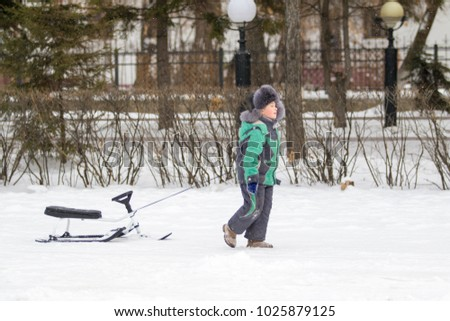 Petropavlovsk, Kazakhstan - February 12, 2018: A boy with a sled rides in the winter from the mountain