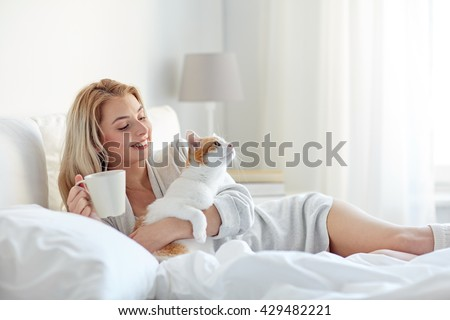 pets, morning, comfort, rest and people concept - happy young woman with coffee cup and cat in bed at home - stock photo