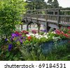 Petunia Flowers in a metal planter by a wooden footbridge over the river Thames in England - stock photo