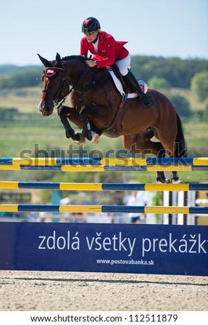 PEZINOK, SLOVAKIA - SEPTEMBER 9: Jorne Sprehe on horse Quisam's Cherie clears a jump on Grand Prix Postova Banka-Peugeot on September 9, 2012 in Pezinok, Slovakia - stock photo