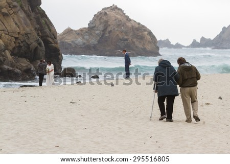 Pfeiffer Beach, California - May 01 : Senior couple enjoying the views of this dramatic beach as a young couple does their wedding photo shoot, May 01 2015 Pfeiffer beach, California.