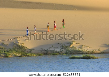 Phan Rang town, Ninh Thuan province, Vietnam - November 26, 2016 : Cham women in traditional dress walking across sand dunes to collecting water near Phan Rang, Vietnam. Many Cham people retain