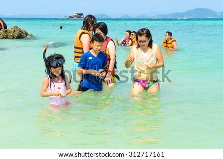 PHANG NGA,THAILAND - MARCH 24 :  Tourists watching the fish and playing sea water happily on the beach in summer at Khai Nok island. - 24 March 2015, Phang Nga, Thailand