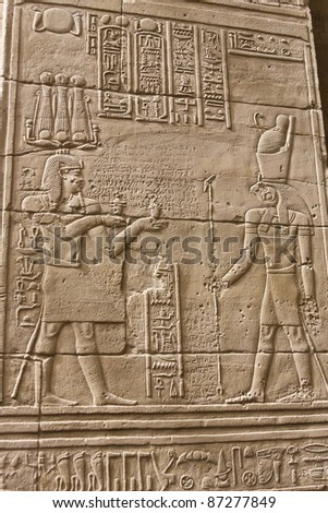 Pharaoh's offering to the falcon-headed god Horus is engraved on the wall of the Philae temple in Egypt - stock photo
