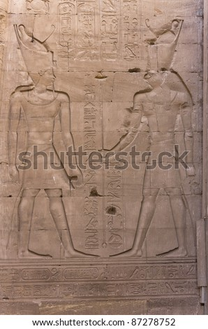 Pharaoh with the Falcon-headed god Horus: engraving on the wall of Edfu temple in Egypt - stock photo