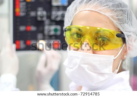 Pharmaceutical Factory Worker. Worker Using Control Panel. A female technician is monitoring the process of pill packaging. - stock photo