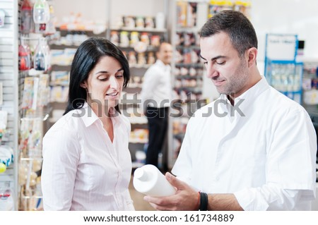 Pharmaceutical giving advice on medication to one customer. In the background we can see another customer - stock photo