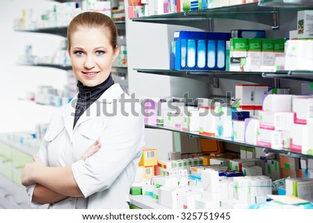 Pharmaceutical industry. Cheerful pharmacist chemist woman standing in pharmacy drugstore - stock photo