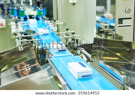 pharmaceutical packing production line conveyer at manufacture pharmacy factory. Authentic shot in challenging conditions. maybe little blurred - stock photo