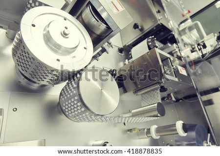 pharmaceutical tablet pill production. blistering packing machine - stock photo