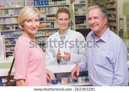 Pharmacist and costumers smiling at camera at pharmacy - stock photo
