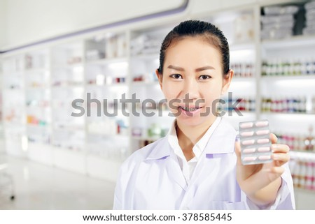 Pharmacist and Doctor woman holding pill in hand , health care and pharmacology concept on medicine cabinet and store medicine and pharmacy drugstore for background - stock photo