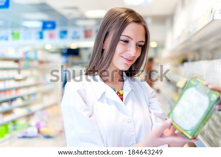 Pharmacist and health care worker in pharmacy with medicine and drugs - stock photo