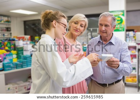 Pharmacist and her customers talking about medication in the pharmacy - stock photo