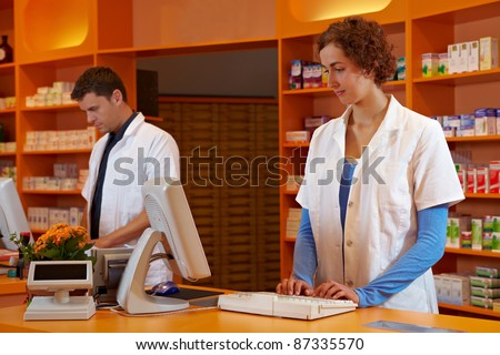 Pharmacist and PTA in pharmacy working behind desk