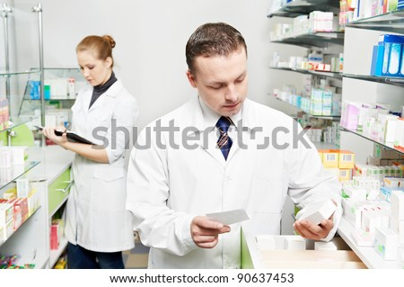 pharmacist chemist man with prescription in pharmacy drugstore - stock photo
