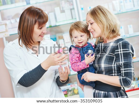 pharmacist chemist woman demonstrating cream gel to child girl with mother in pharmacy drugstore. family health - stock photo
