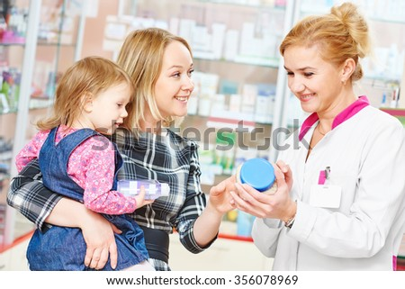 pharmacist chemist woman demonstrating vitamin to child girl with mother in pharmacy drugstore. family health