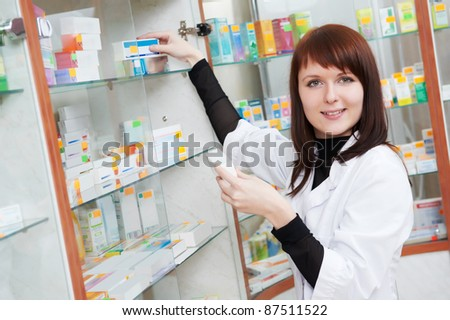 pharmacist chemist woman looking for medicine in pharmacy drugstore with recipe - stock photo