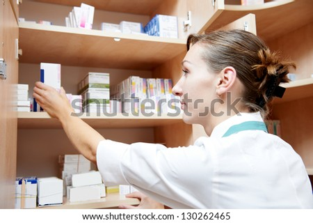 pharmacist chemist woman marking drugs in pharmacy drugstore warehouse - stock photo