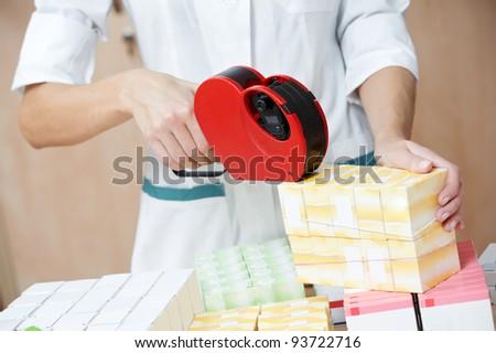 pharmacist chemist woman marking drugs in pharmacy drugstore warehouse - stock photo