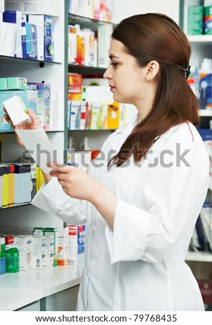 pharmacist chemist woman standing in pharmacy drugstore with recipe - stock photo