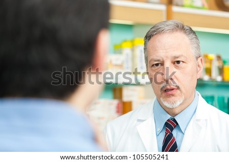 Pharmacist dealing with a customer - stock photo