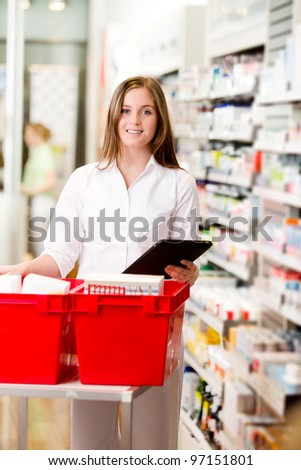 Pharmacist filling a prescription from a digital tablet - stock photo