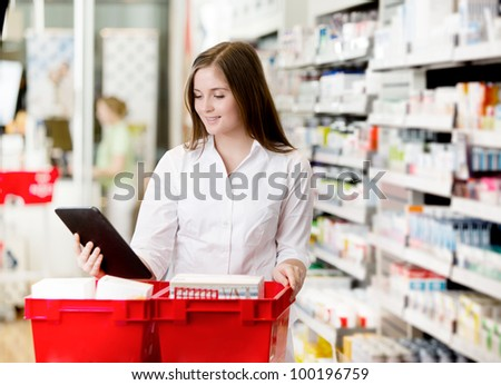 Pharmacist filling prescriptions looking at digital tablet - stock photo