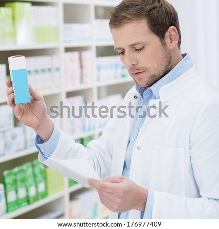 Pharmacist fulfilling a prescription holding medication in his hand as he checks the script - stock photo