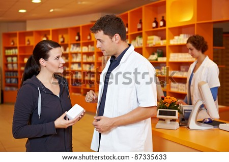 Pharmacist giving advice and selling to female customer in pharmacy - stock photo