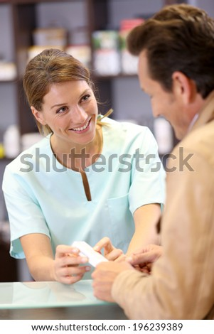 Pharmacist giving advice to customer on medication - stock photo