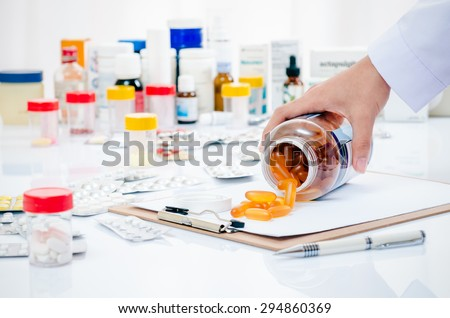 pharmacist hand holding medicine container on a folder - stock photo