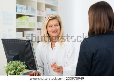 Pharmacist helping a customer in the pharmacy smiling as she takes payment for medication from a woman with her back to the camera - stock photo