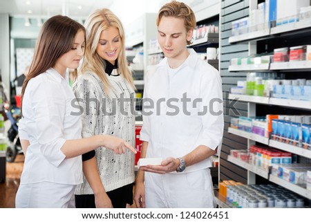 Pharmacist helping womain in drug store - stock photo