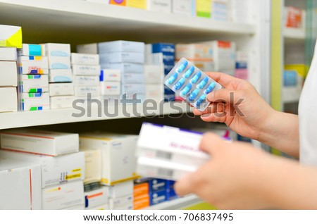 Pharmacist holding medicine box and capsule pack in pharmacy drugstore.