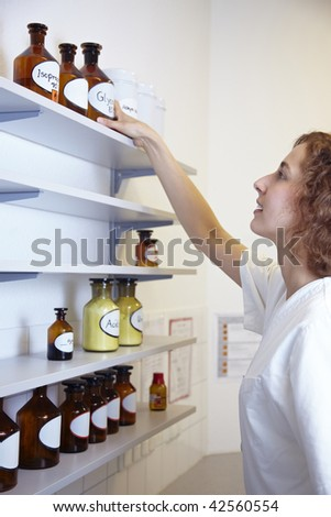 Pharmacist in lab reaching for bottle with alcohol