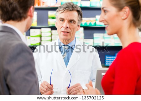 Pharmacist is consulting customers - a man and a woman - in his pharmacy - stock photo